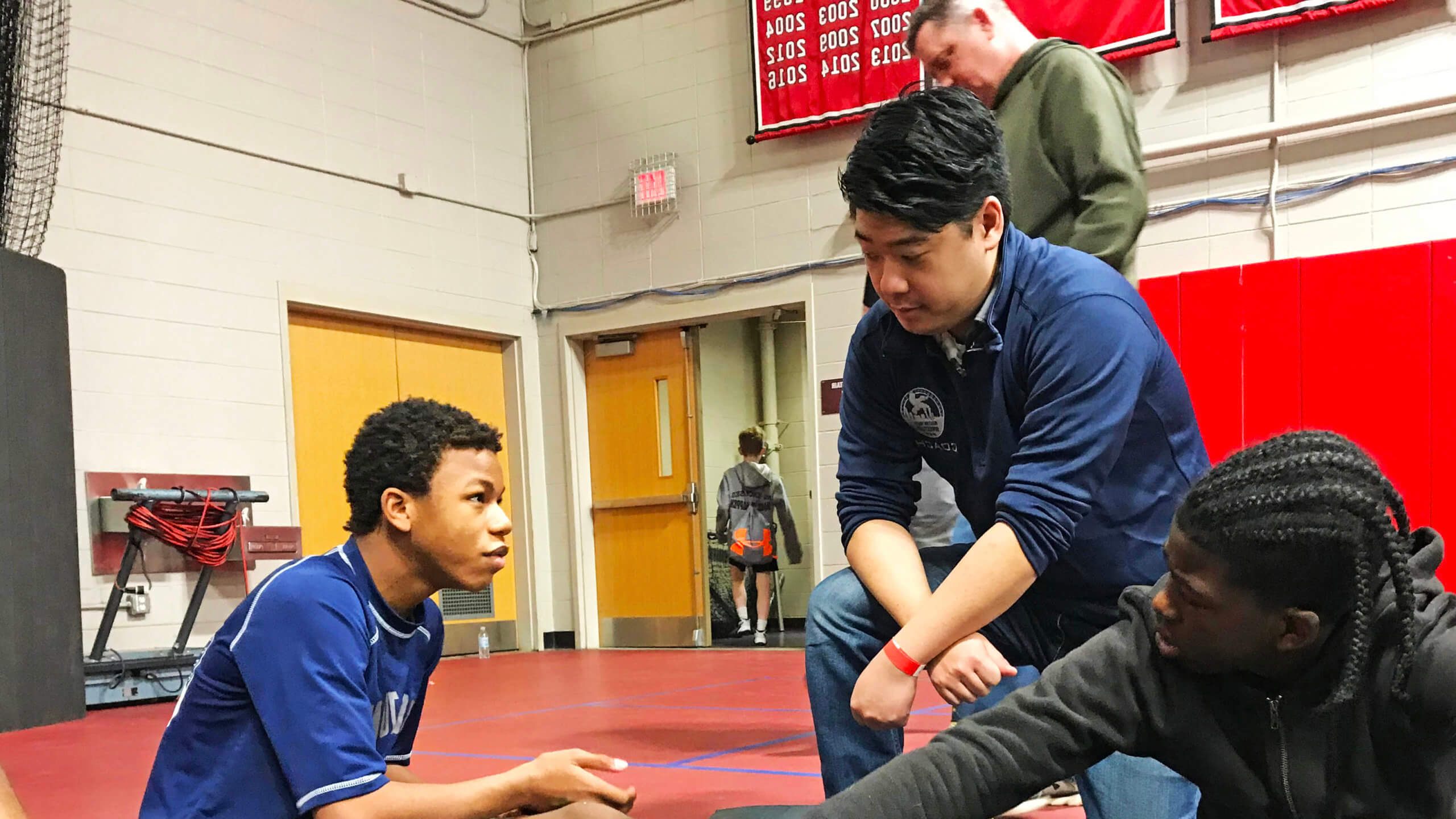 Photo of alumnus Addison Ray '15 at a youth wrestling event
